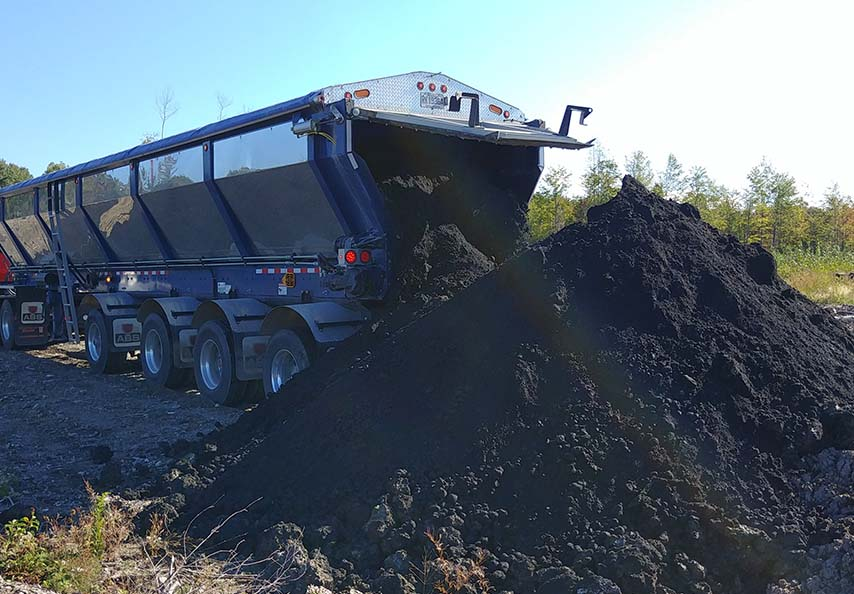 Municipal biosolids and liming materials from pulp and paper plants are delivered directly to the forest areas prior to being spread.  Photo courtesy of Domtar
